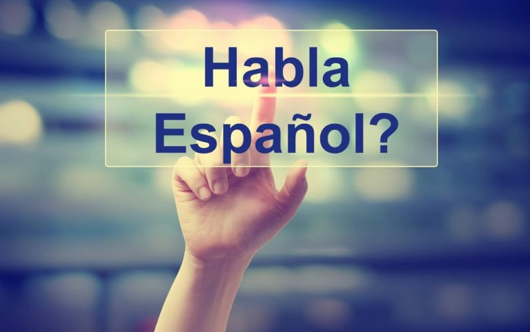 "A hand touching a screen displaying ""Habla Espanol?"""