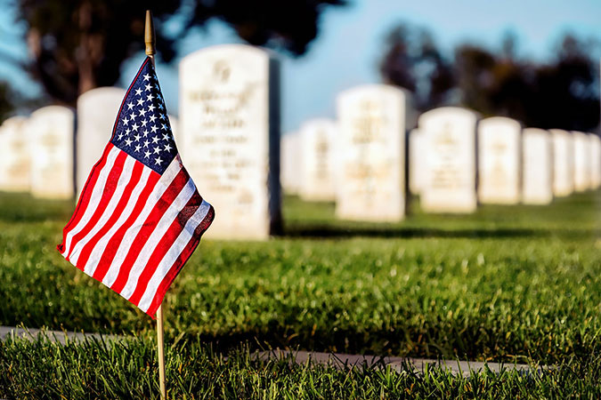 A flag on a grave at a veterans national cemetery.
